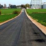 Droga Rokszyce - Oprzężów - nowy asfalt, w oddali widać rozbudowywane magazyny firmy Kaufland w Rokszycach