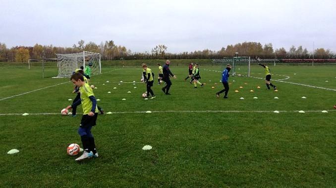 Młodzi piłkarze LKS Wola Krzysztoporska podczas treningu na boisku - slalomy z piłkami
