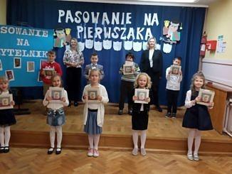 """Grupa dzieci w strojach galowych wraz z dwiema nauczycielkami stoi na tle dekoracji z napisem """"Psowanie na pierwszaka""""; obok napis """"pasowanie na czytelnika""""; dzieci trzymaja w dłoniach sestawy książekstoi na"""