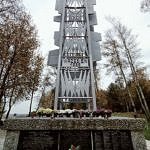 Pomnik Bohaterów Września 1939 r. w Borowej. Metalowa, wysoka konstrukcja. Pomnik ozdobiony chryzantemami w doniczkach