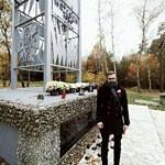 Sołtys Parzniewiczek Adam Zajączkowski przed pomnikiem Bohaterów Września 1939 r. w Borowej. Na pomniku stawione chryzantemy i znicze