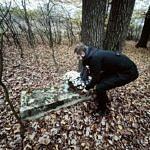 Sołtys Parzniewiczek Adam Zajaczkowski składa kwiaty na leśnej mogile