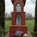 Kapliczka z brązowej cegły klinkierowej (za szybką Matka Boska) ozdobiona chryzantemami w doniczkach