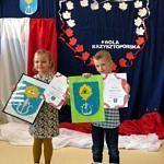Dziewczynka i chłopiec prezentują wykonane własnoręcznie herby gminy Wola Krzysztoporska