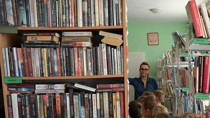 regały z książkami; w tle bibliotekarka