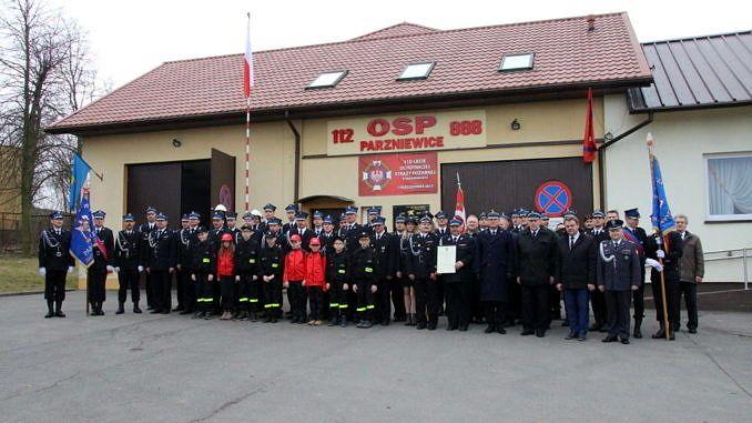 Członkowie jednostki OSP Parzniewice w mundurach (także członkowie drużyny młodzieżowej w czerwonych dresach) stoja przed budynkiem OSP Parzniewice