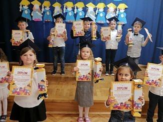 Grupa maluchów w strojach galowych biretach z dyplomami w dłoniach