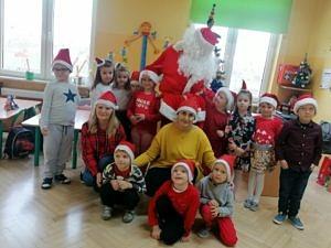 Dzieci w mikołajkowych czapkach z Mikołajem i wychowawczynią