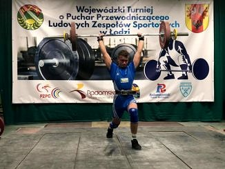 Zawodnik w niebieskiej koszulce podnosi sztanę; w tle baner z napisem Wojewódzki Turniej o Puchar Przewodniczącego LZS w Łodzi