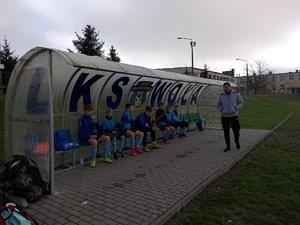 Zawodnicy siedzą pod wiatą z napisem LKS Wola; przed nimi stoi trener