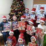 Grupa dzieci w mikołakowych czerwono-białych czapeczkach stoi przy choince; dzieci trzymaja w dłoniach kalendarze adwentowe