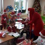 Mikolaj w czerwonym stroju rozdaje słodycze dzieciom siedzącym w ławkach