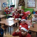 Dzieci w mikołajkowych czapkach siedzą w ławkach