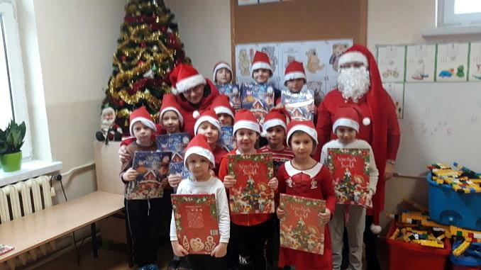 Grupa dzieci w mikołakowych czerwono-białych czapeczkach stoi przy choince; dzieci trzymaja w dłoniach kalendarze adwentowe; obok stoi Mikołaj