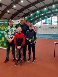 Na hali sportowej stoją trzej chłopcy z mistrzem świata Pawłem Fajdkiem