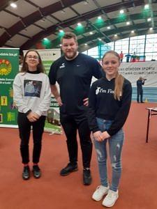 Dwie dziewczynki stoją z mistrzem świata Pawłem Fajdkiem