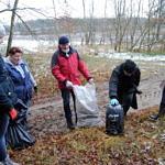 Ludzie z workami zbierający śmieci w lesie