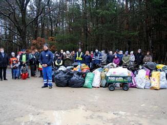 Grupa ludzi na tle lasu. Na czele sołtys Borowej Artur Jędrzejczyk i wójt Roman Drozdek. Przed nimi kilkanaście worków śmieci i wózek załadowany odpadami
