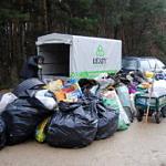 Worki ze śmieciami obok przyczepki samochodowej oznaczonej logo Leszy Bełchatów
