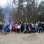 Grupa ludzi na tle lasu. Obok rozpalone ognisko
