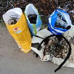 Trzy kolorowe worki ze śmieciami; obok druty, stae dętki