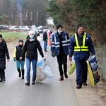 Grupa ludzi z workami na śmieci idzie droga wzdłuż lasu