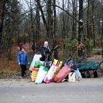 Grupa ludzi przy wokach z zebranymi śmieciami