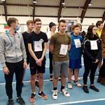 Grupa młodych sportowców stoi na hali; na piersiach numery startowe