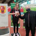 Na trzecim stopniu podium dziewczynka z Bujen w czarnym stroju przybija pięść z Markiem Mazurem z rady wojewódzkiej zrzeszenia LZS