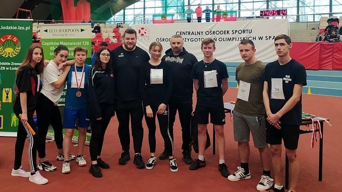 Grupa młodych lekkoatletów z ZS CKZ Bujny z trenere. W środku stoimistrz świata w rzucie młotem Paweł Fajdek