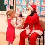Mikołaj wręcza prezent dzieciom