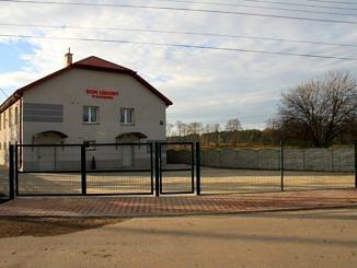 Widok Domu Ludowego w Kacprowie, a przed nim utwardzony kostką betonową teren i nowe ogrodzenie panelowe z bramą i furtką
