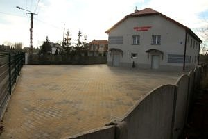 Widok Domu Ludowego w Kacprowie, a przed nim utwardzony kostką betonową teren