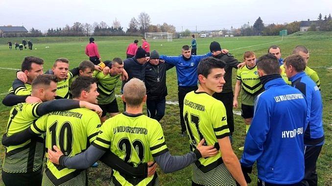 Grupa piłkarzy LKS Wola Krzysztoporska w seledynowych koszulkach razem z trenerem stoi w kręgu; piłkarze trzymają się za ramiona