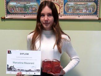 Marcelina Mazerant - dziwczynka z długimi włosami ciemny blond w białym golfie trzyma w dłoniach duplom i ststuetkę zdobytej nagrody