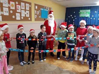 Grupa dzieci z Mikołajem - trzymają kolorowy łańcuch z papieru