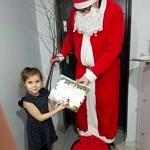 Mikołaj w czerwonym stroju wręcza dziewczynce certyfikat
