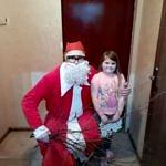 Mikołaj kuca i obejmuje małą dziewczynkę