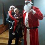 Sołtys Blizina Kamila Kaczorowska w czerwonej długiej mikołajowej czapce z dzieckiem na ręku z Mikołajem w czerwonym stroju