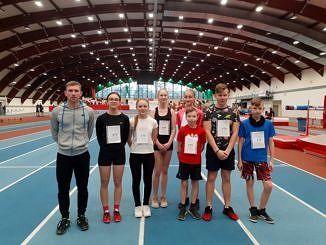 Grupa młodych lekkoatletów z numerami sartowymi na piersiach stoi z trenerem na dużej hali sportowej o półokrągłym sklepieniuz trenerem
