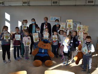 Grupa dzieci wraz z członkami jury stoi z dyplomami w dłoniach. Przed nimi siedzi olbrzymi pluszowy miś.