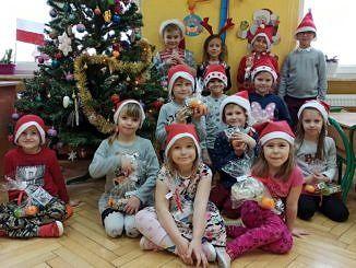 Dzieci w mikołajkowych czapkach przy choince