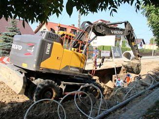 Na pierwszym planie żółta koparka - prace przy budowie kanalizacji