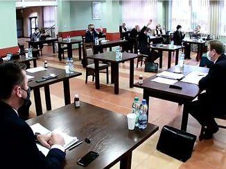 Sesja Rady Gminy Wola Krzysztoporska. Radni i władze gminy siedzą przy oddzielnych stolikach w maseczkach