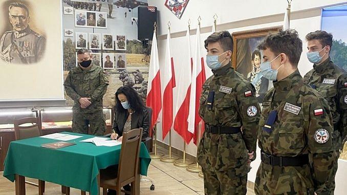 Dyrektor ZS CKZ Bujny podpisuje porozumienie w obecności wojskowego i uczniów z oddziału przygotowania wojskowego, którzy obo stoja w mundurach