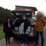 Autorka Danuta Stępień, sołtys Jadwiga Kauc i młody mężczyzna przy otwartym bagażniku samochodu z książkami