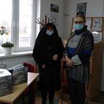 Danuta Stępień przekazuje egzemplarze książki do biblioteki w Woźnikach