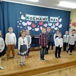 Grupa dzieci w strojach galowych stoi na scenie; z tyłu na niebieskim tlw napis Kochamy Was i serduszka