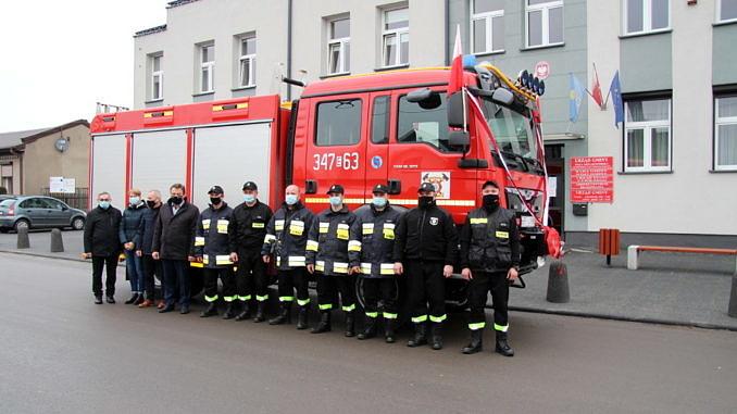 Nowy samochód ratowniczo-gaśniczy a przed nim grupa strażaków i przedstawicieli Urzędu Gminy Wola Krzysztoporska