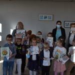Grupa dzieci - przedszkolaków obdarowanych książkami z wyprawki czytelniczej; z tyłu stoją opiekunki i bibliotekarki
